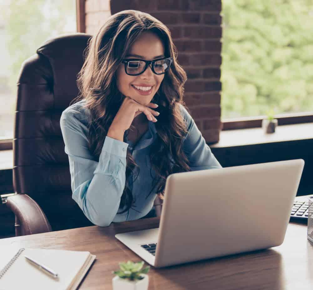 happy woman looking at her WordPress website on her laptop